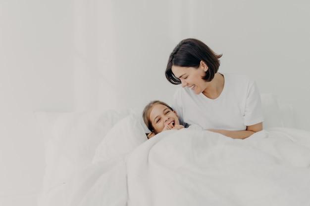 Giocosa madre premurosa e sua figlia rimangono a letto a lungo, posano sotto una coperta soffice, godono il buongiorno, hanno sorrisi felici sui volti