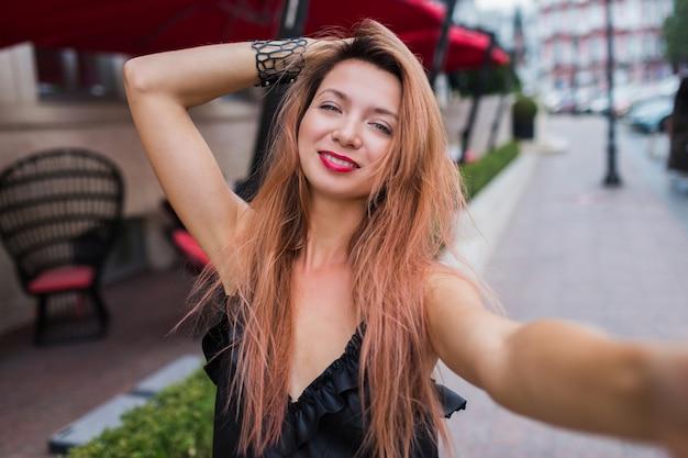 Giocoso carino rosso sente donna con sorridente che fa autoritratto e godersi le vacanze estive in europa. immagine esterna positiva. abito nero, labbra rosse.