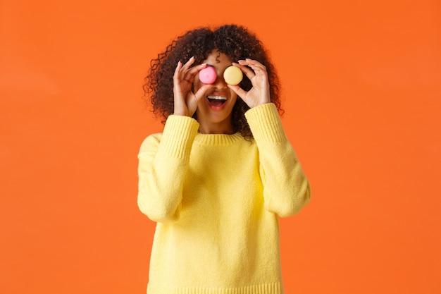 Giocoso divertente e spensierata, bella ragazza riccia afro-americana in maglione giallo, scherza intorno fa gli occhi da macarons e sorride, mangia dolci, come dessert, in piedi arancione