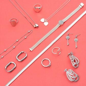 Gioielli in argento su sfondo rosa minimale