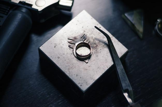 Gioielli in metallo, non rifiniti da un maestro su un supporto metallico. utensili da gioielliere, bruciatori e pinze