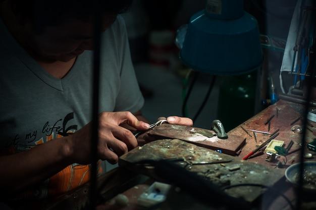 Gioielliere dietro il vetro. lavora con gioielli