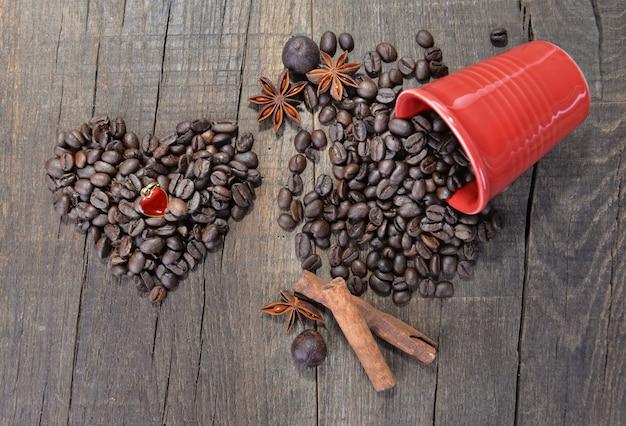 Gioiello a forma di cuore in chicchi di caffè che formano un cuore accanto a una tazza rossa rovesciata piena di fagioli su fondo di legno