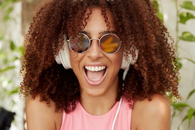 Gioiosa adorabile femmina afroamericana in tonalità tiene la bocca aperta, ride allegramente, ascolta la musica preferita ad alto volume in cuffia. la donna dalla pelle piuttosto scura gode dell'audio dalle trasmissioni radiofoniche.