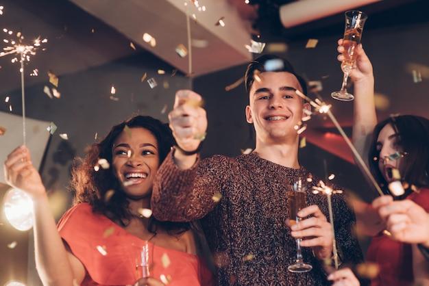 Gioiosa e felice. amici multirazziali festeggiano il nuovo anno e tengono in braccio luci e bicchieri di bengala