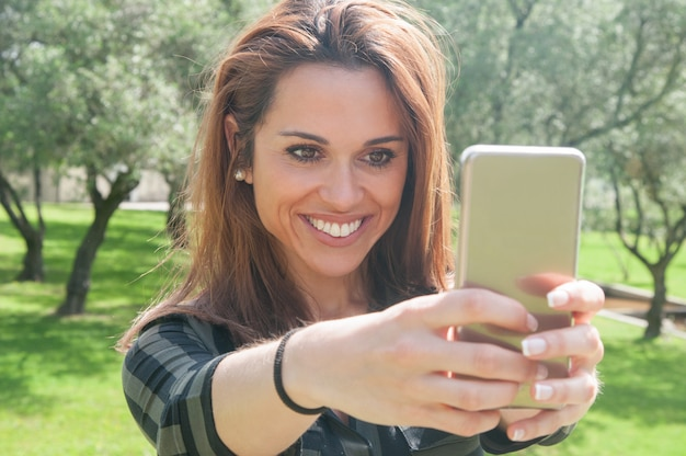 Gioiosa giovane donna eccitata prendendo selfie nel parco