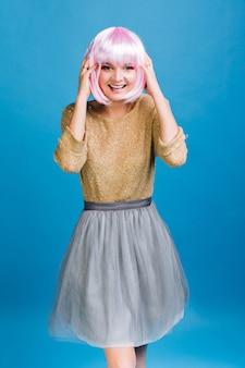 Gioiosa giovane donna in maglione dorato brillante, gonna in tulle grigio con capelli tagliati rosa divertirsi sullo spazio blu.