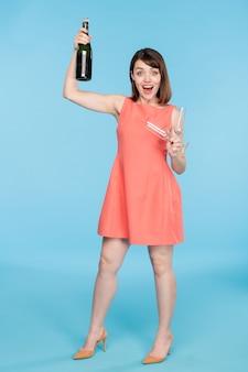 Gioiosa giovane femmina pin-up in vestito rosso che tiene due flauti e una bottiglia di champagne