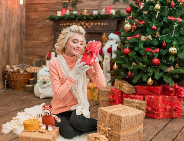 Gioiosa ragazza femminile che indossa abiti invernali, seduto vicino all'albero di natale, tenendo confezione regalo.