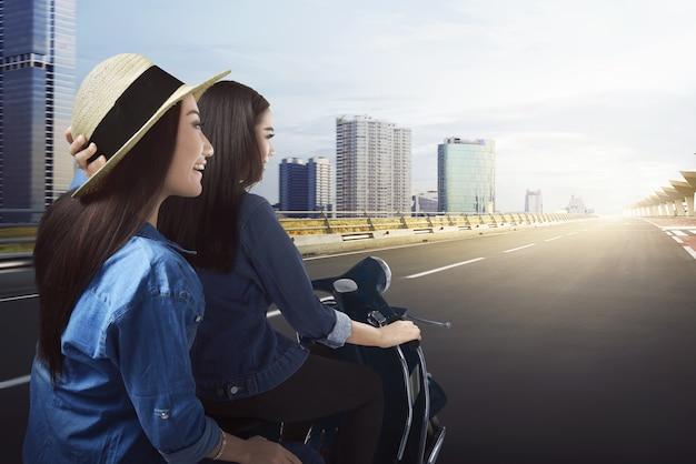 Gioiose due ragazze asiatiche che viaggiano in scooter