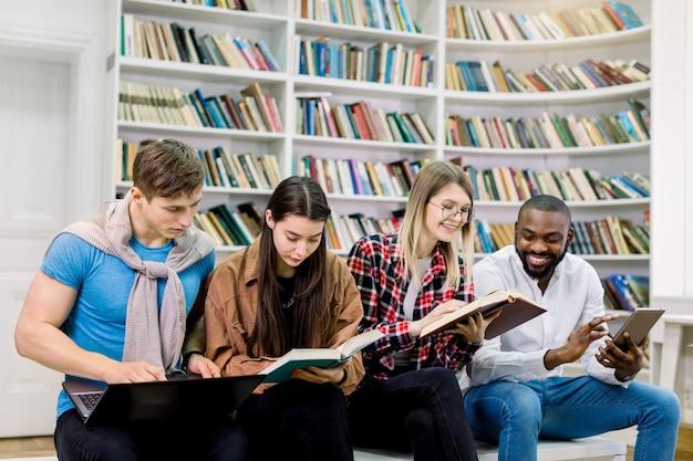 Gioiosi studenti multietnici ragazzi e ragazze, seduti su una panchina in biblioteca e in possesso di libri tradizionali e lettore di e-book, tablet, pc touchpad