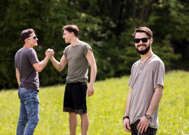 Gioioso giovane in piedi sul picnic con gli amici