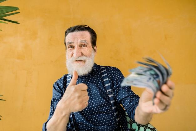 Gioioso uomo anziano con la barba ben curata, indossando abiti alla moda, tenendo un sacco di soldi di carta, banconote da un dollaro e mostrando il pollice in su