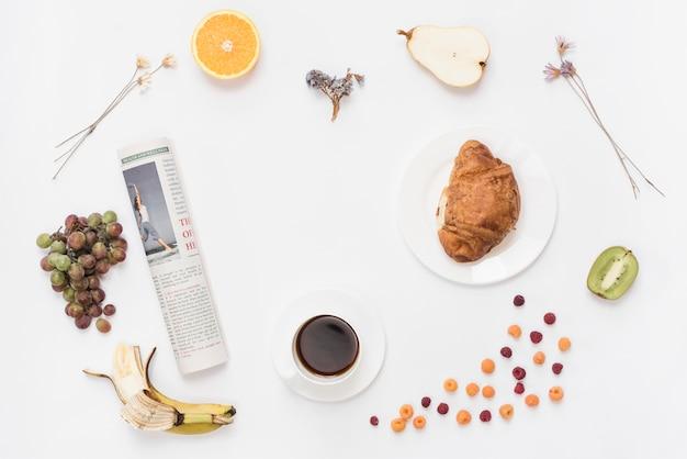 Giornale arrotolato con tazza di caffè; croissant e frutta su sfondo bianco