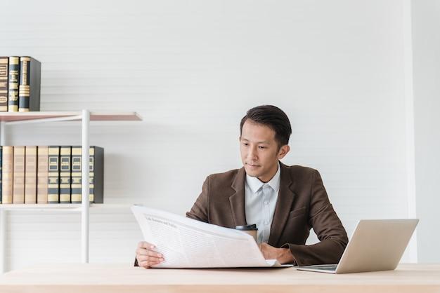 Giornale della lettura dell'uomo d'affari al suo scrittorio