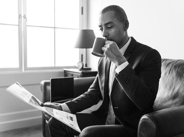 Giornale della lettura dell'uomo d'affari e caffè