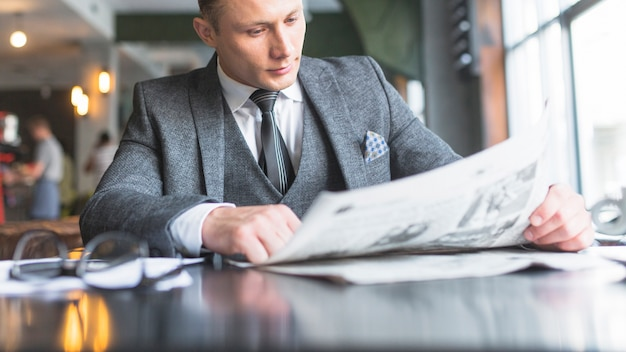 Giornale della lettura dell'uomo d'affari nel caf�