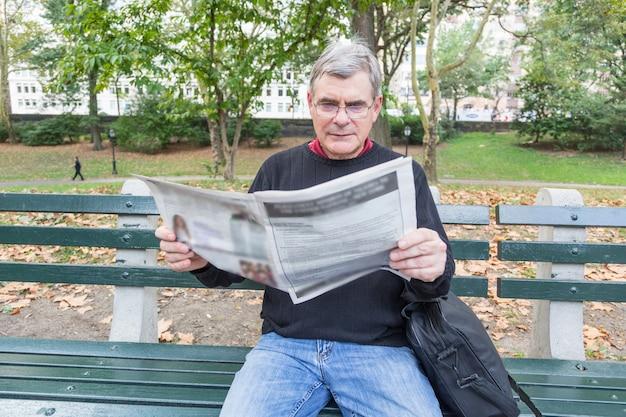 Giornale della lettura dell'uomo senior al parco