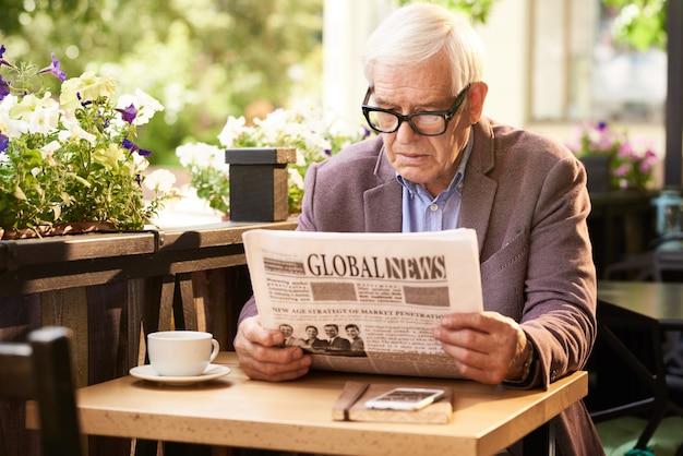 Giornale della lettura dell'uomo senior in caffè all'aperto