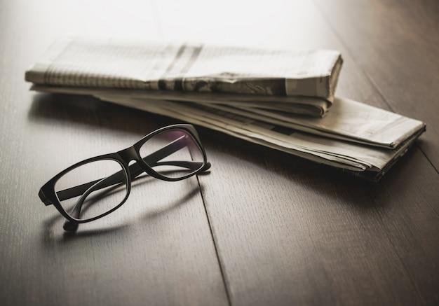 Giornale e vetri di lettura sul fondo del giornale di affari dello scrittorio di affari