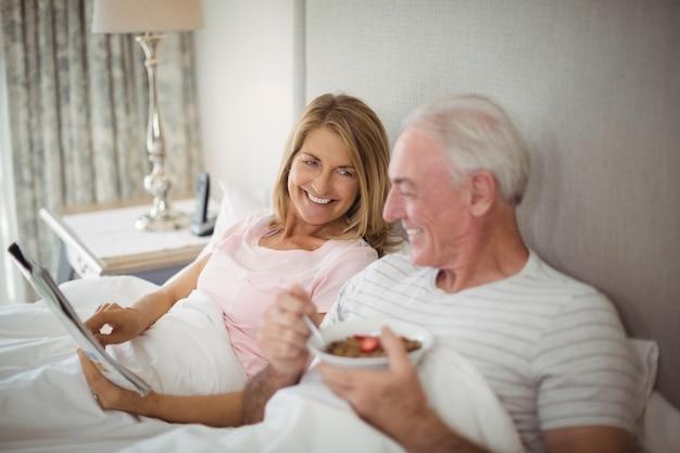 Giornale sorridente della lettura delle coppie mentre mangiando prima colazione