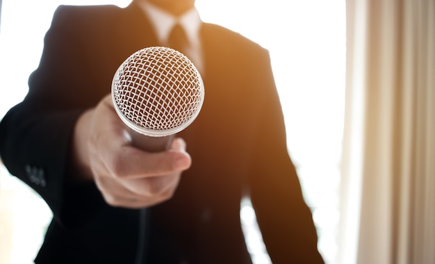 Giornalisti che archiviano il microfono intervistando l'uomo d'affari