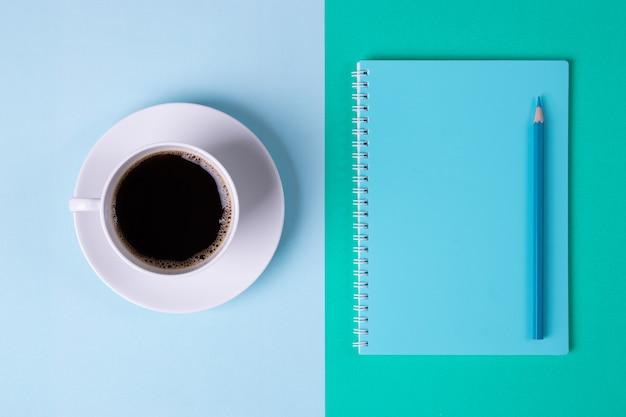 Giornata degli insegnanti. caffè nero e taccuino blu sulla tavola blu e verde pastello.