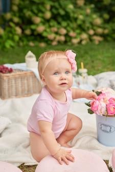 Giornata dei bambini, una bambina nel parco si siede in un cestino con amaretti in un picnic estivo