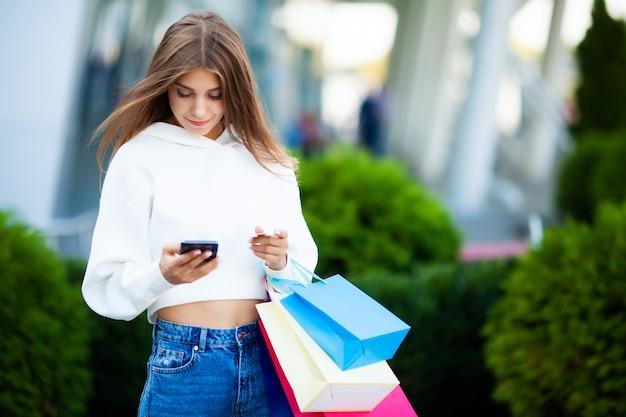 Giornata di shopping. sacchetti colorati della holding della donna vicino al suo centro commerciale shooping nella festa nera di venerdì.