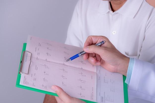 Giornata mondiale del cuore. aggiusti le mani con il grafico del cardiogramma con la penna. cardiologo che spiega i risultati del suo paziente ecg.