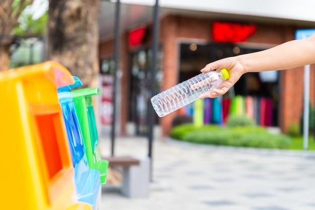 Giornata mondiale dell'ambiente, mano della donna che tiene e che mette i rifiuti della bottiglia di plastica nella spazzatura tr