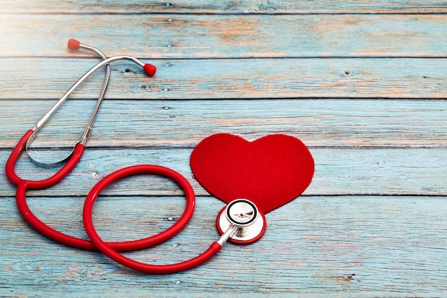 Giornata mondiale della salute, assistenza sanitaria e concetto medico, stetoscopio rosso e cuore rosso su fondo di legno blu