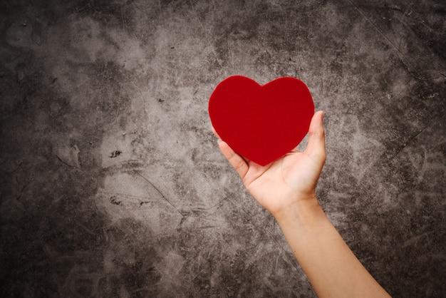 Giornata mondiale della salute, la mano delle donne tiene il cuore rosso su sfondo nero grunge