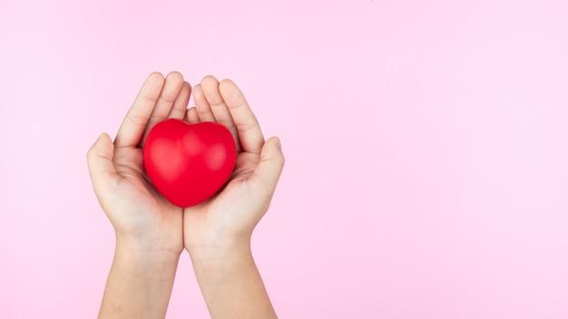Giornata mondiale della salute, mani del bambino che tengono il cuore rosso, assistenza sanitaria, amore e concetto di assicurazione familiare