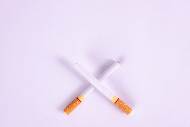 Giornata mondiale senza tabacco, due tagli incrociati di sigarette, concetto di non fumare su sfondo bianco.