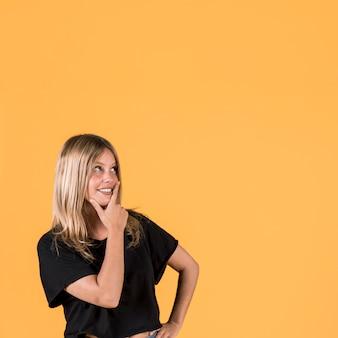 Giorno che sogna giovane donna sorridente che controlla contesto giallo