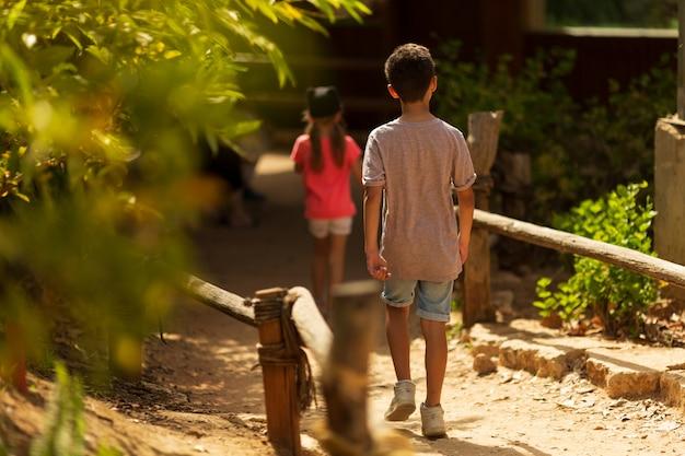Giorno dei bambini. ragazzino e ragazza che corrono nel parco. vista posteriore