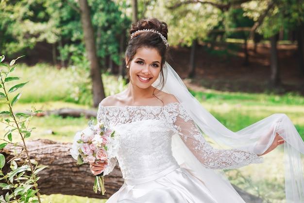 Giorno del matrimonio. giovane bella sposa con acconciatura e trucco in posa in abito bianco e velo.
