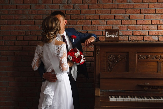 Giorno del matrimonio. gli sposi si abbracciano e si baciano al coperto. abbracci appassionati di una coppia amante del matrimonio in interni eleganti.