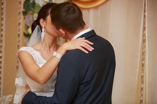 Giorno del matrimonio. gli sposi si baciano durante la cerimonia del matrimonio. abbracci appassionati di una coppia amorosa. sposo con asola che abbraccia delicatamente la sposa con bouquet.wedding momento romantico rosso. novelli sposi