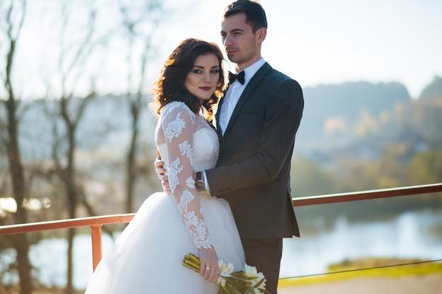 Giorno del matrimonio. matrimonio. passeggiata nuziale all'aperto. sposi novelli con bouquet di fiori. ritratto di sposi. amore, sentimenti, tenerezza. legame matrimoniale