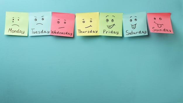 Giorno della settimana ed espressione del viso. adesivi colorati su un blu