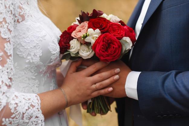 Giorno delle nozze all'aperto. momento romantico del matrimonio. il ritratto della sposa e dello sposo si tiene per mano delicatamente. sposi con bouquet da sposa rosso da vicino