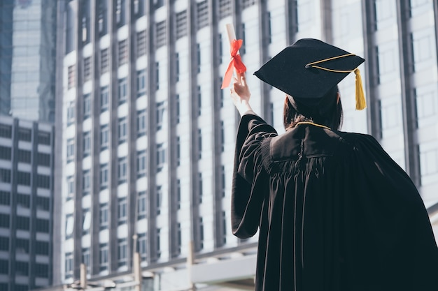 Giorno di laurea, vista posteriore della donna asiatica con cappello di laurea e abito in possesso di diploma