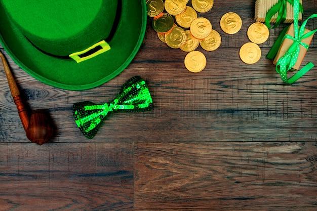 Giorno di san patrizio. cappello verde del leprechaun, farfallino verde, tubo di fumo e monete di oro su fondo di legno