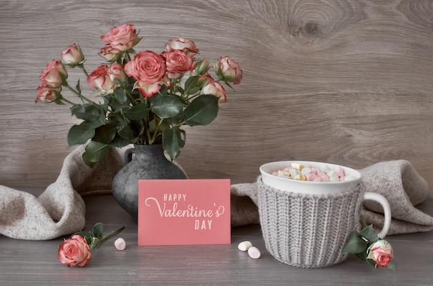 Giorno di san valentino natura morta con tazza di cioccolata calda con marshmallow, rose rosa e biglietto di auguri con il testo