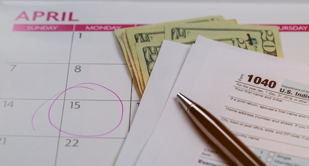 Giorno fiscale, dollari e modulo modulo imposta sul reddito 1040 che mostra il giorno fiscale per il calendario di aprile con le parole