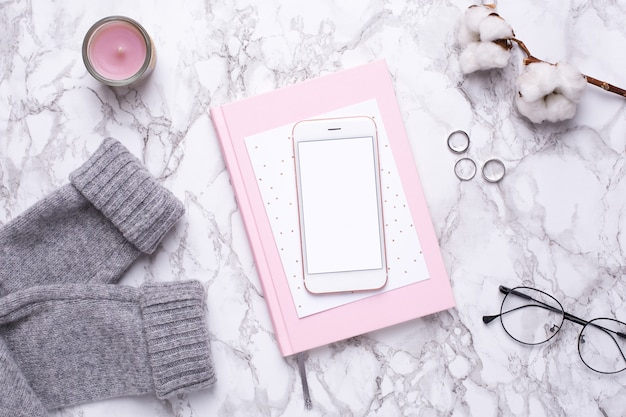 Giorno lavorativo delle donne con il telefono cellulare e taccuino rosa sulla tavola di marmo