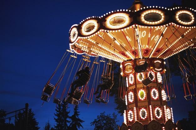Giostra carosello nel parco divertimenti di notte città
