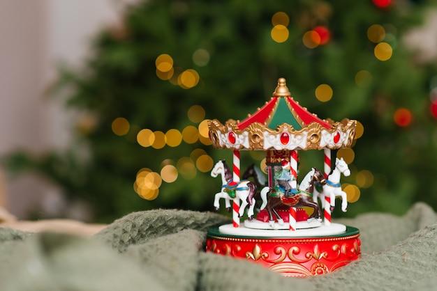 Giostra musicale giocattolo di natale sullo sfondo delle luci accese dell'albero di natale.